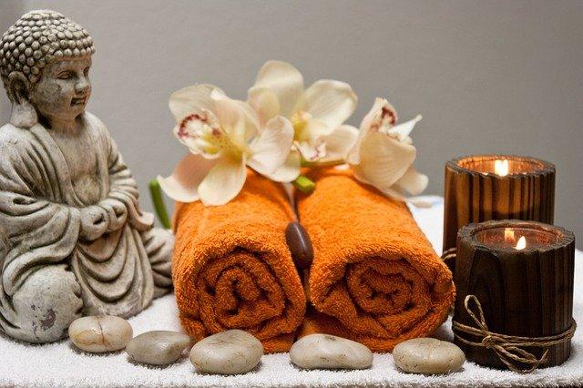 Unser Körper möchte, dass es uns gut geht.  Bild mit einer Buddhafigur, Kerzen, Steinen und zwei gerollten Handtüchern, sinnbildlich für Ruhe und Entspannung.  Quelle: Nico H. auf Pixabay